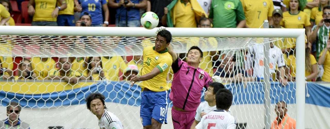 Paulinho briga pela bola pelo alto junto com o goleiro Kawashima
