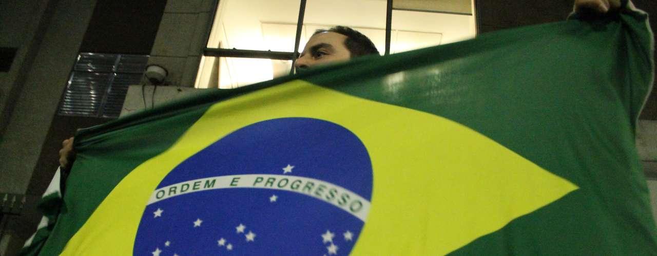17 de junho - Manifestante levanta bandeira do Brasil durante passeata contra o aumento das passagens do transporte público na região da Faria Lima, na zona oeste de São Paulo