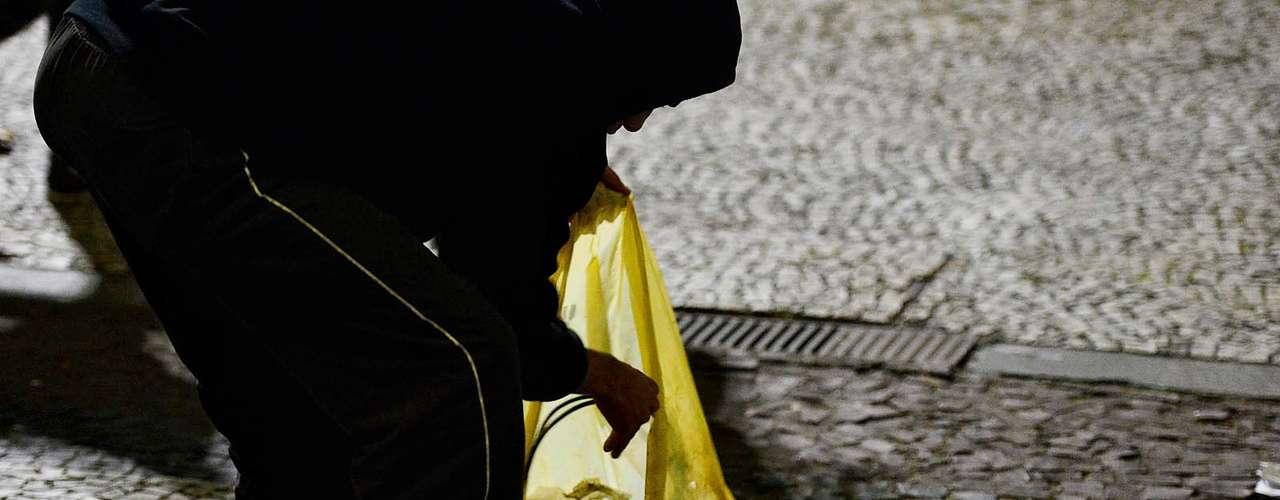 18 de junho - Homem esvazia saco de lixo e guarda dois monitores LCD no centro de São Paulo
