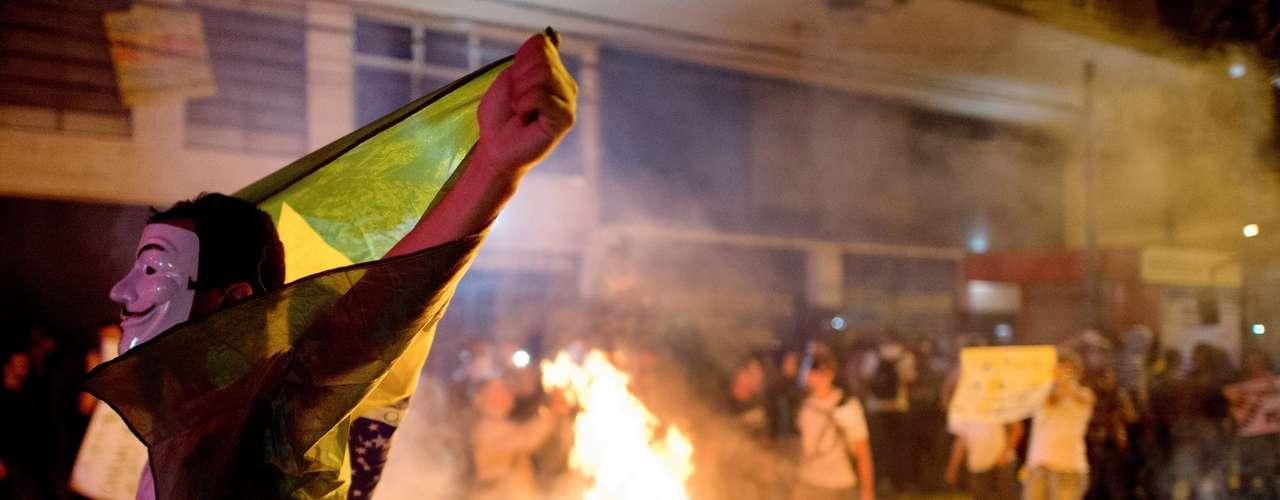 19 de junho -Manifestante abre a bandeira do Brasil em frente a fogueira durante confronto com a polícia, em Niterói