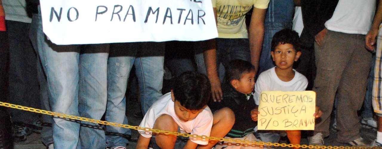 28de junho -Crianças bolivianas acendem vela durante protesto em frente à 49º DP