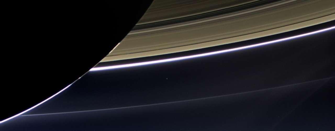 22 de julho - Rara imagem feita no dia 19 de julho pela lente grande-angular da sonda Cassini mostra os anéis de Saturno com o planeta Terra e a Lua ao fundo: um mesmo ponto brilhante à distância de 1,5 bilhão de quilômetros