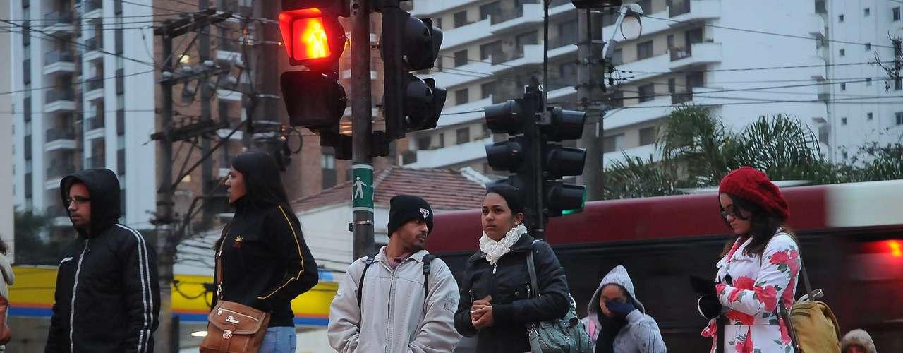 26 de julho -Pedestres enfrentam frio e chuviscona avenida Santo Amaro, zona sul de São Paulo, na manhã desta sexta-feira
