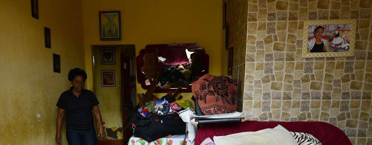 Moradora mostra os estragos sofridos em sua casa