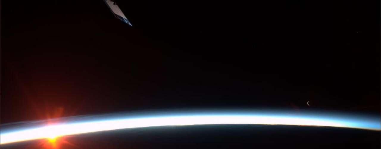 O nascer do Sol sobre o horizonte ainda obscuro - com a Lua ao fundo - foi registrado pela astronauta americana Karen Nyberg, única mulher atualmente a bordo da Estação Espacial Internacional. O limiar do dia na Terra é conferido de perto pelos integrantes da Expedição 36 cerca de 15 vezes a cada 24 horas