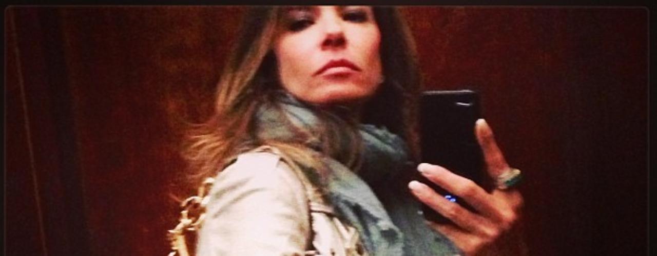 Luciana Gimenez posa foto de look do dia com jaqueta de couro, echarpe e bolsa com couro de cobra