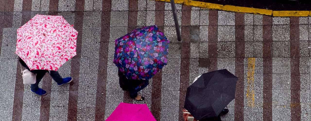 13 de agosto -  Pedestres se protegem da chuva em Caxias do Sul, na Serra Gaúcha. A temperatura chegou a 8°C na cidade