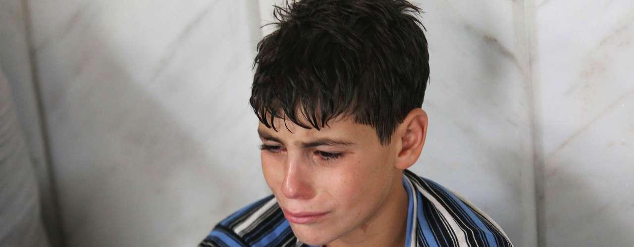 Menino chora após o ataque que, segundo a oposição, deixou centenas de mortos em Damasco