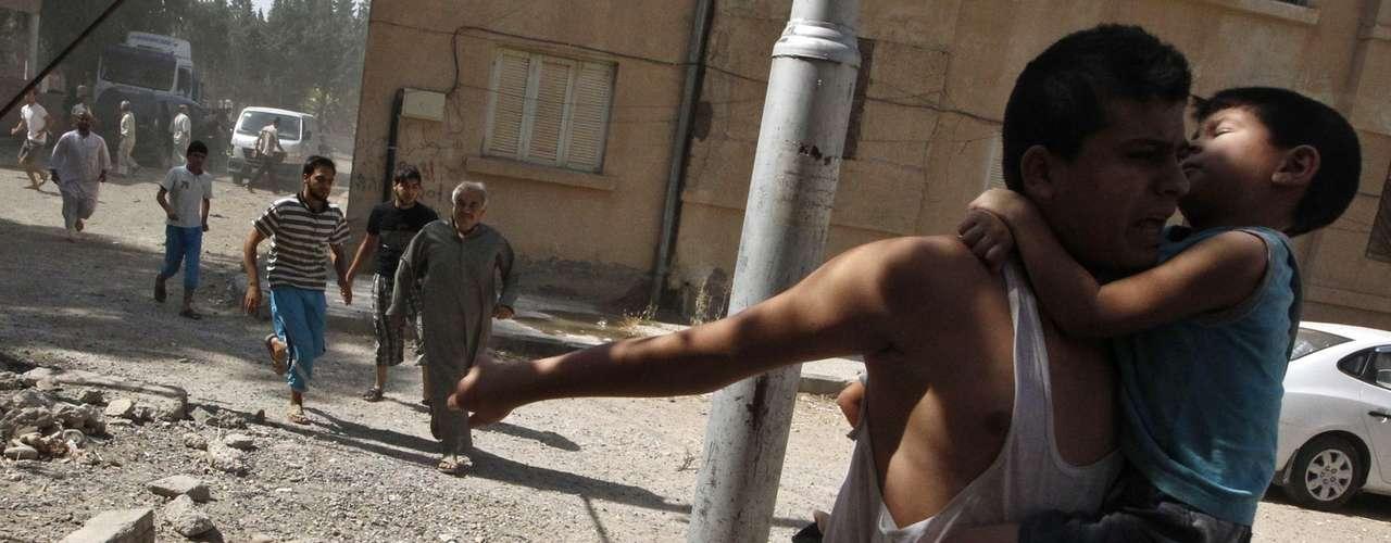 Após o ataque com armas químicas, homem corre com criança nos braços