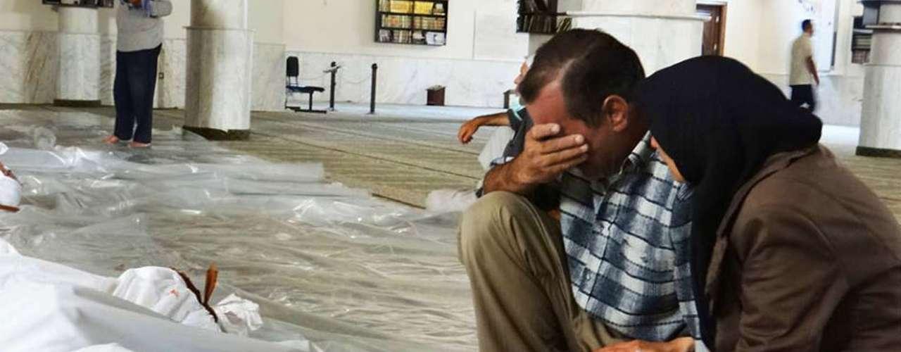Foto do Comitê Local de Arbeen, órgão da oposição síria, mostra homem e mulher chorando sobre corpos de vítimas do suposto ataque químico das forças de segurança do presidente Bashar al-Assad
