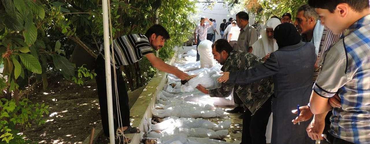 Nesta fotografia do Comitê Local de Arbeen, cidadãos sírios tentam identificar os mortos do suposto ataque químico das forças de segurança do presidente Bashar al-Assad
