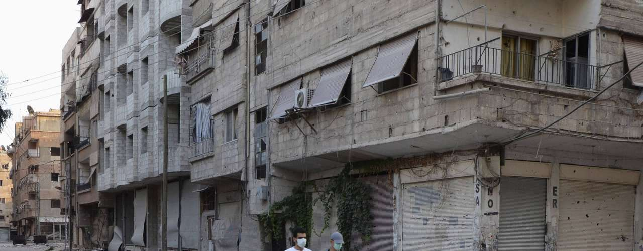 Homens usam máscara para se proteger de possíveis gases químicos ao se aventurarem por rua da área de Ain Tarma