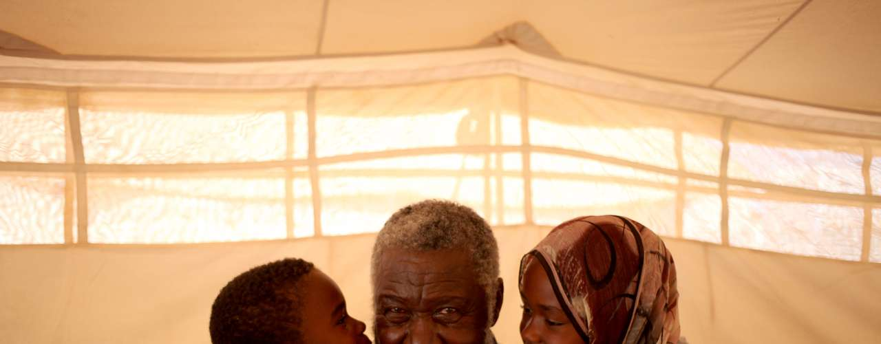 Mohammed Abdullah, 75 anos, recebe beijo dos seus netos Rashed, 7 anos, e Afrah, 11 anos. \