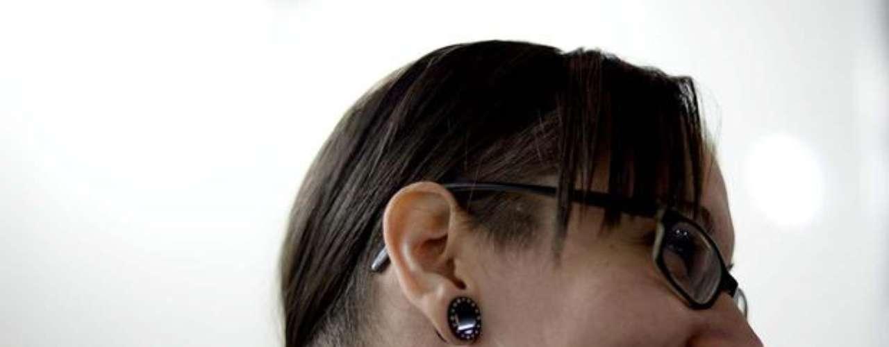 Mulher mostra tatuagem feita na lateral esquerda do pescoço. Além da rosa, há buracos que parecem ter sido feitos na pele