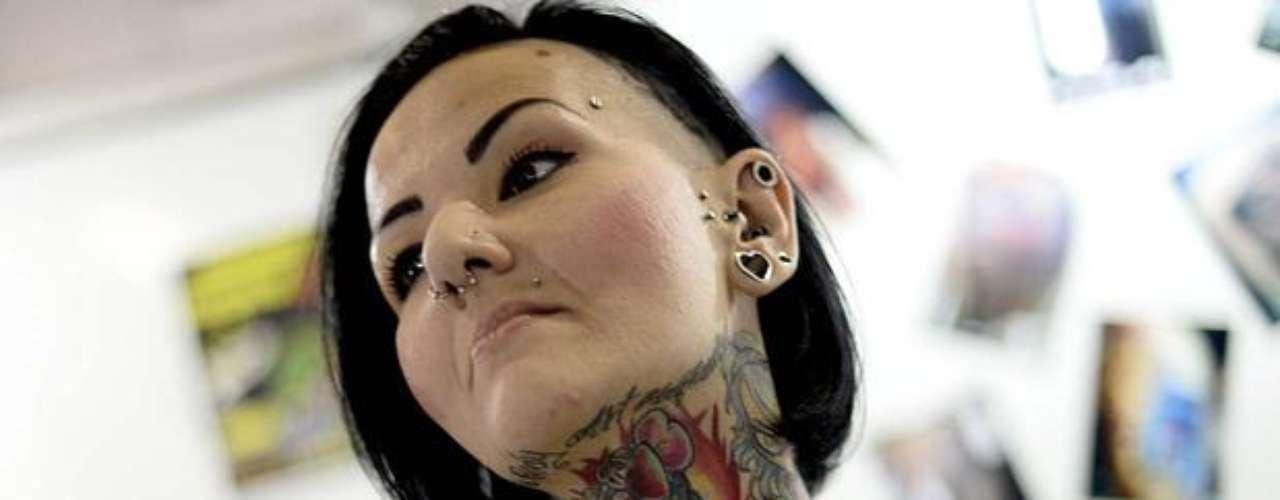 Apesar de coloridos, desenhos feitos em mulher participante da Tattoo Week não são nada femininos e cobrem colo e pescoço