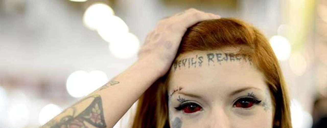 Difícil falar o que chama mais atenção na mulher participante da Tattoo Week 2013, se os olhos tatuados de vermelho ou a frase Devil's Rejected (rejeitada pelo diabo) escrita na testa