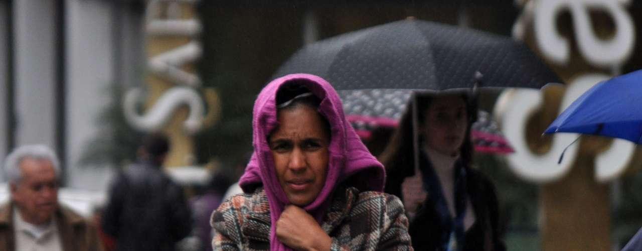 7 de outubro - Mulher se protege na capital paulista com a tarde de outubro mais fria desde 2010