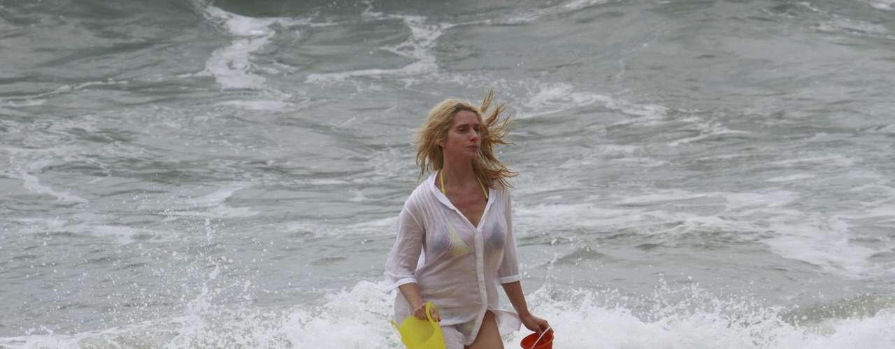 Outubro 2013-Letícia Spiller aproveitou a folga nas gravações de 'Joia Rara' para aprender a surfar, nesta terça-feira (15), na Prainha, no Rio de Janeiro. Ao lado de um rapaz, a atriz primeiro praticou os movimentos do esporte na areia, para em seguida se arriscar no mar. Depois do treino, ela ainda relaxou na areia ao lado do filho, Pedro
