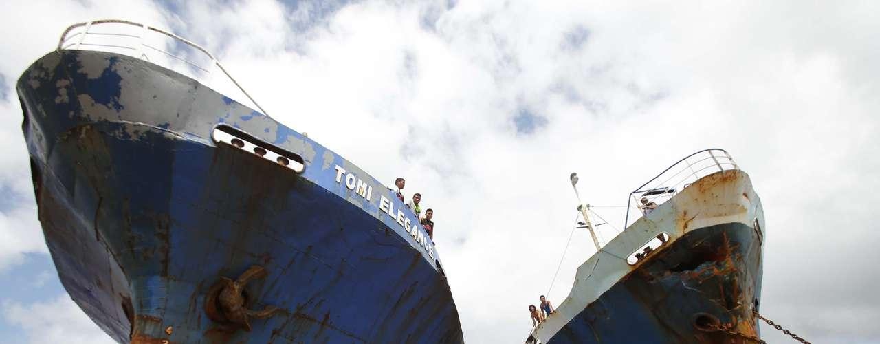 10 de novembro - Sobreviventes passam por dois grandes navios que foram arrastados pelas fortes ondas causadas pelo tufão Haiyan na cidade de Tacloban