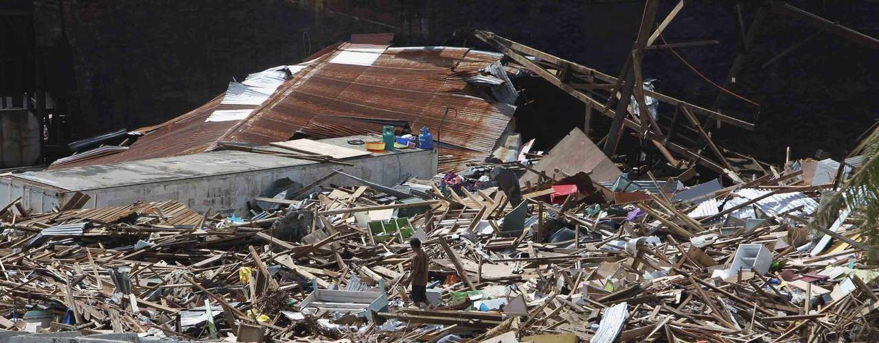 10 de novembro -Sobrevivente caminha por destroços após passagem do tufão