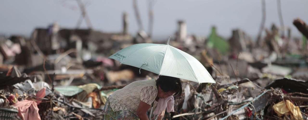 11 de novembro -Em meio aos destroços, sobrevivente tenta resgatar pertences em Tacloban