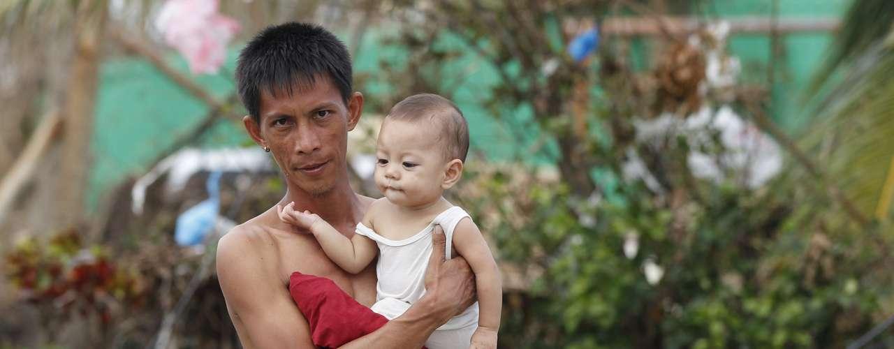 11 de novembro -Roy Cagbian, 28 anos, segura sua filha de 7 meses Shandev em frente ao que restou da sua casa em Tacloban