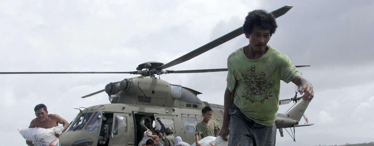 11 de novembro -Moradores retiram sacos de mantimentos dos helicópteros da Força Aérea na vila de Capiz, no centro das Filipinas