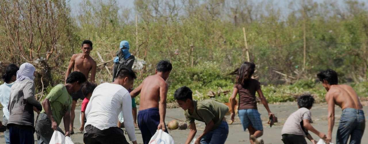11 de novembro -Moradores carregam sacos de mantimentos em Capiz