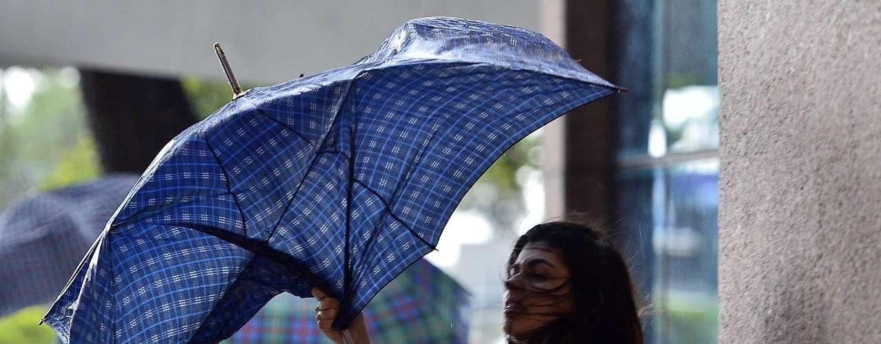 12 de novembro - Pedestre luta contra o vento no centro do Rio de Janeiro