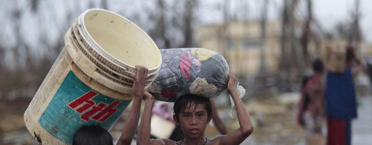 12 de novembro -Crianças carregam aquilo que conseguem salvar entre os amontoados de destroços