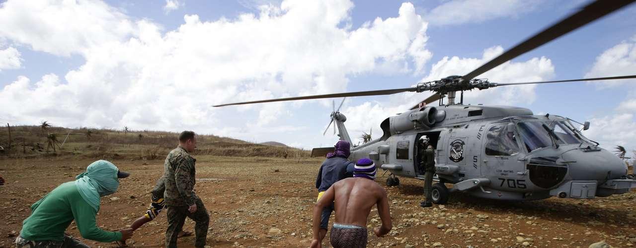 16 de novembro -Helicóptero da Marinha dos EUA chega com suprimentos paramoradores que estavam em regiões isoladas após a passagem,semana passada, do tufão Haiyan. Moradores correm em direção a aeronave para receber os mantimentos