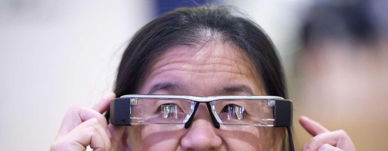Visitante testa os óculos inteligentes Epson Moverio BT-200 durante a CES. O aparelho projeta duas imagens idênticas nas lentes, formando uma figura semitransparente no campo de visão do usuário. O aparelho roda Android e está em pré-venda nos EUA por US$ 699