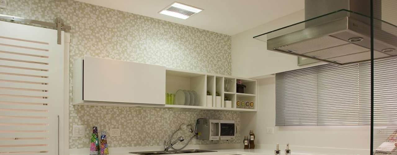 A arquiteta Cinthia Garcia e a designer Andréia Karalkovas apostaram em cozinha americana com piso de porcelanato e pastilhas brancas e transparentes, além de bancada da pia de corian branco