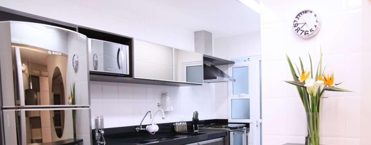 A cozinha americana tem piso e azulejo na cor branca, pia preta e móveis escuros. O projeto é da arquiteta Cinthia Garcia e a designer Andréia Karalkovas