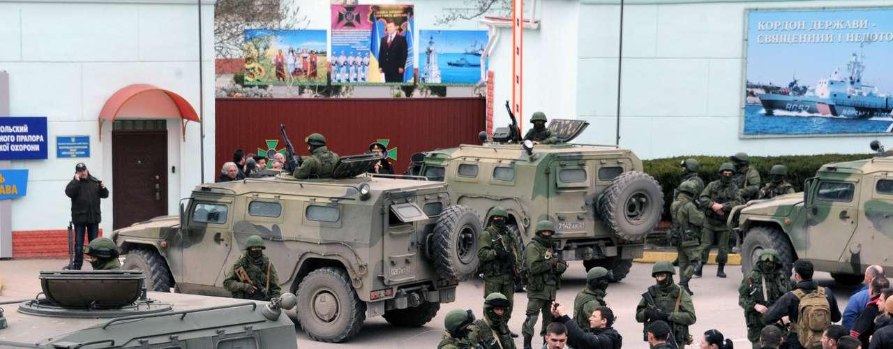1 de março de 2014 -Pessoas olham para homens não identificados em uniforme militar bloqueando uma base da unidade de guarda fronteira ucraniana em Balaclava
