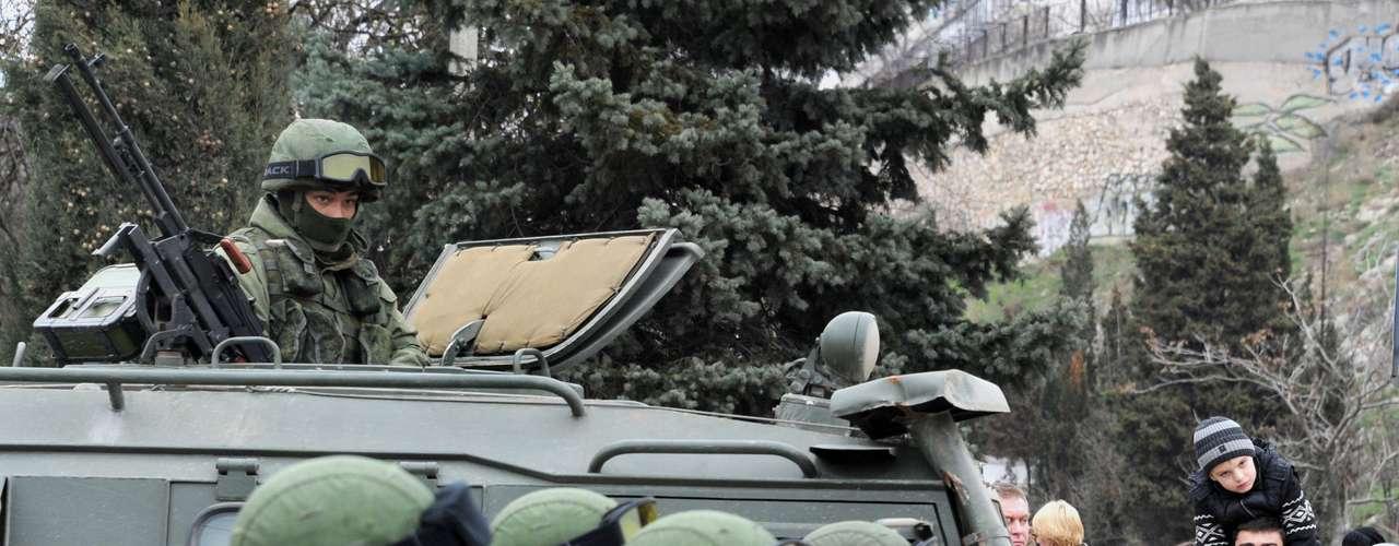 1 de março de 2014 -Tropas comuniformes sem identificação ficam de guarda em Balaclava, nos arredores de Sevastopol, Ucrânia. Um emblema em um dos veículos identifica-os como sendo pertencentes ao exército russo. Autoridades ucranianas acusaram a Rússia de enviar novas tropas para Crimeia, uma região estratégica da Rússia que abriga uma grande base naval