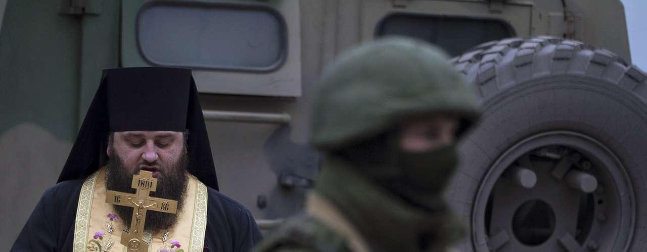 1 de março de 2014 -Religioso ortodoxo reza próximo aos militares uniformizados emcidade daCrimeia. O senado da Rússia autorizou a invasão de tropas russas à Ucrânia neste sábado, 1 de março