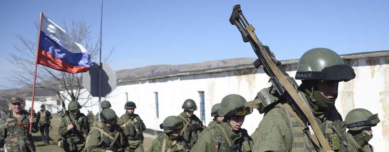 3 de março de 2014 -Homens uniformizados seguram bandeira russa em base militar na vila de Perevalne, próximo a Simferopol. Cerca de mil homens armados se colocaram próximos à brigada naval da Ucrânia desde ontem. Tropas russas e aviões militares ultrapassaram as fronteiras estabelecidas na Crimeia nesta segunda-feira