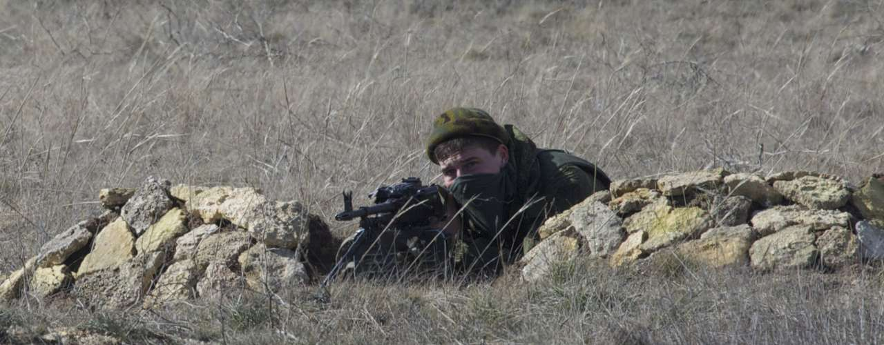 3 de março de 2014 -Soldado pró-Rússia aponta arma para base naval ucraniana na vila de Novoozerne, que fica cerca de 90km da capital da Crimeia. Forças russas estão controlando uma região estratégica do país