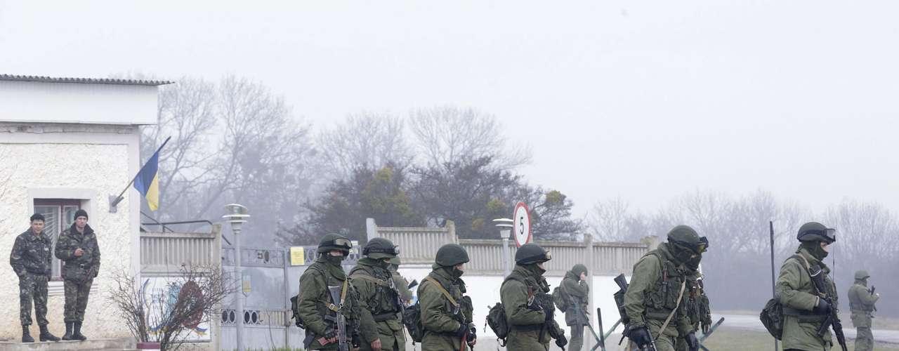 7 de março de 2014 - Doissoldados ucranianos observam enquantoumgrupo de militares armadoscaminha próximo a um acesso à basemilitar localizada emPerevalnoye, nos arredoresde Simferopol, na Crimeia