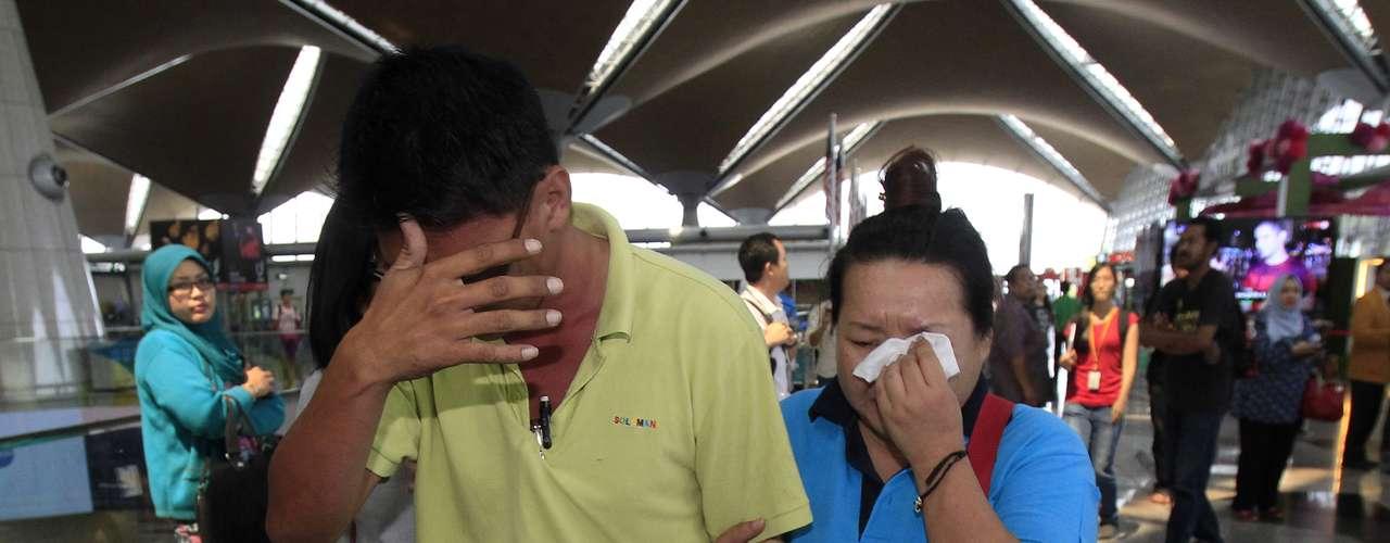 Parentes choram ao sair do local onde familiares e amigos dos passageiros do avião da Malaysia Airlines estão sendo recepcionados, no aeroporto de Kuala Lumpur, na Malásia