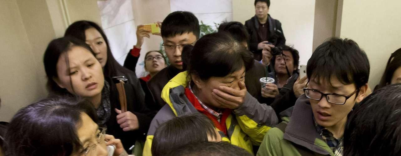 Uma mulher, cercadapela mídia, cobre o rosto em sua chegada em um hotel que está preparado para receberparentes eamigos dos passageiros a bordo doavião desaparecido.Pequim, China, sábado, 8 de março