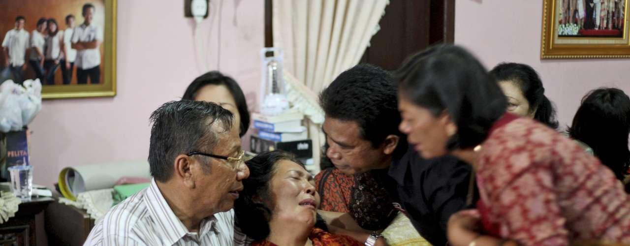 9 de março -Familiares confortam Chrisman Siegar, a esquerda, e sua esposa Herlina Panjaitan, parentes de Firman Siregar, um dos passageiros do voo MH370 da Malaysia Airlines,desaparecido desde a noite de sexta-feira, em sua residência em Medan, Sumatra do Norte, na Indonésia