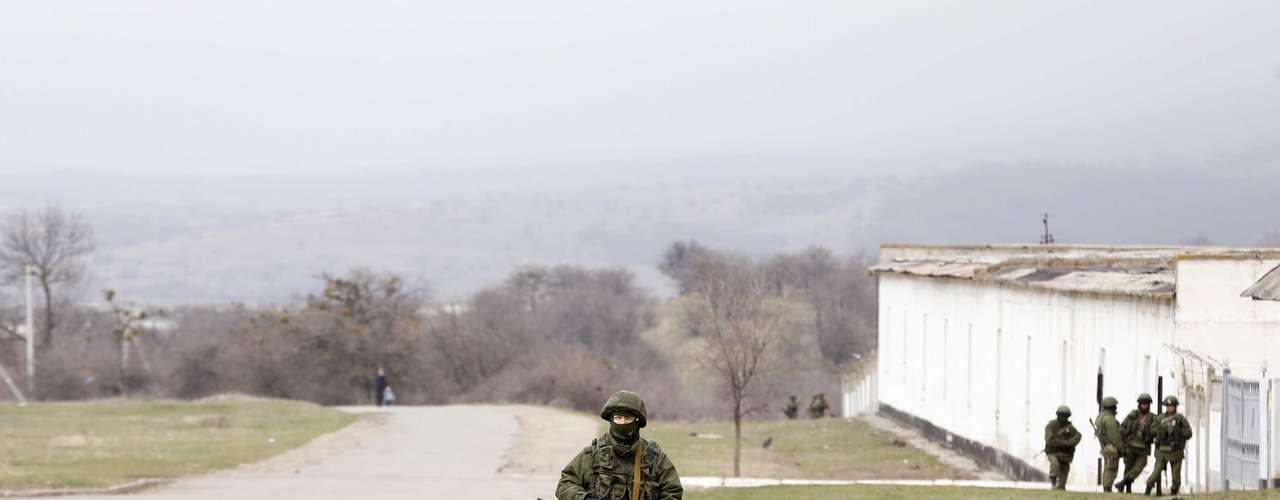 11 de março - Homem armado, possivelmente russo, é visto do lado de fora de uma unidade militar da Ucrânia na vila de Perevalnoye nesta terça-feira