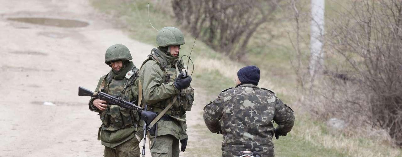 11 de março - Homens armados, possivelmente russos, conversam próximo à base militar ucraniana em Perevalnoye, que fica próxima à Simferopol