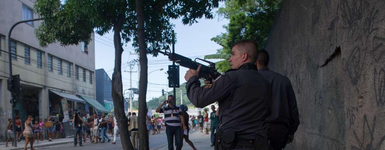 Policial aponta arma durante o protesto dos moradores