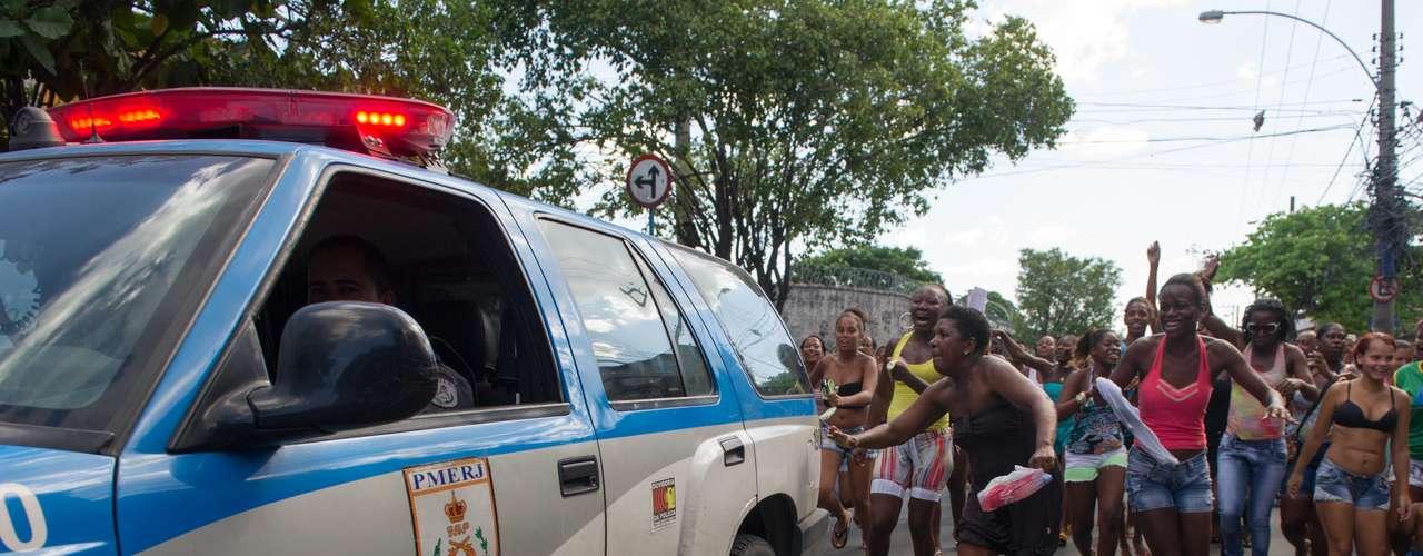 Moradores correm carro da Polícia Militar durante protesto em Madureira