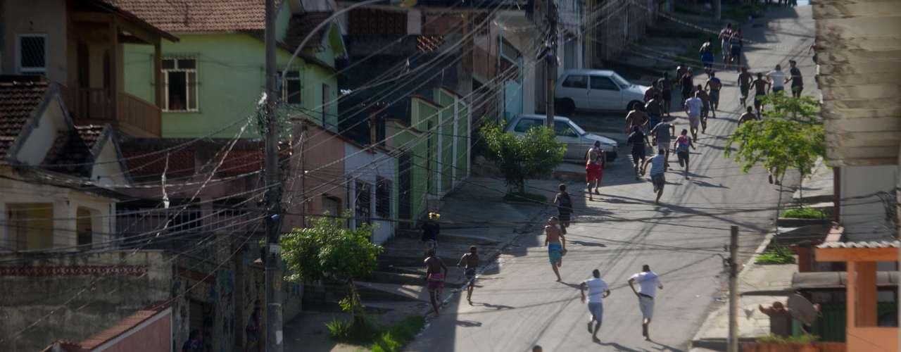 Moradores correm durante protesto contra a morte da moradora, que foi arrastada por uma viatura policial durante tentativa de resgate da vítima