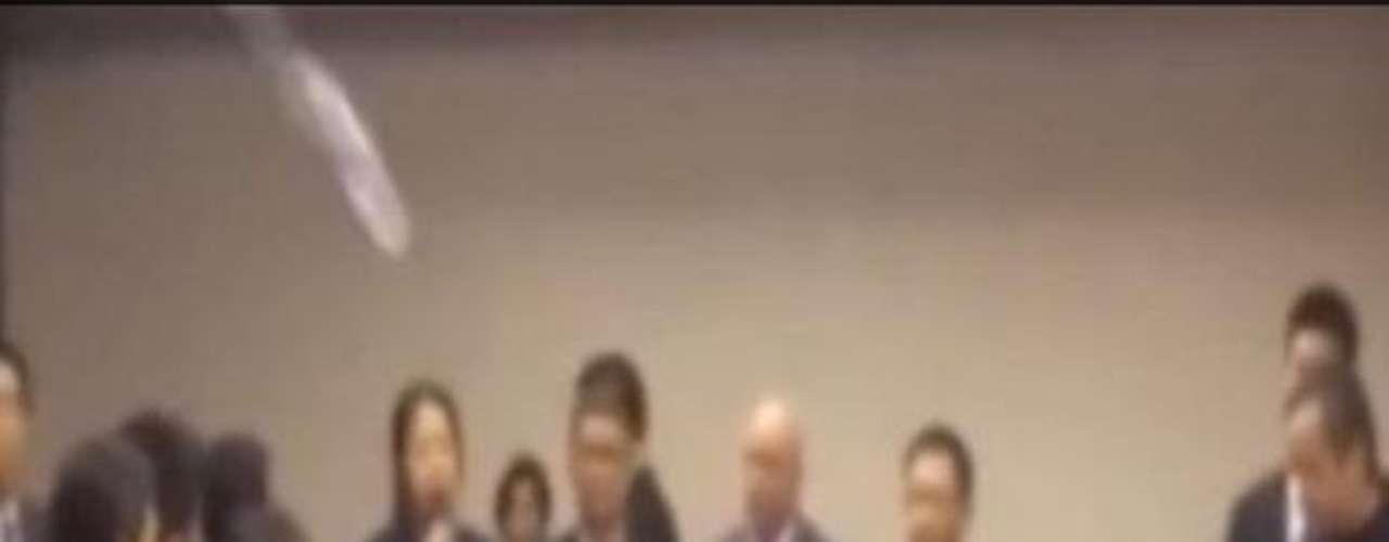 12 de março - Famílias chinesas arremessaram garrafas de água em autoridades, durante entrevista coletiva, na manhã de 12 de março, em Pequim