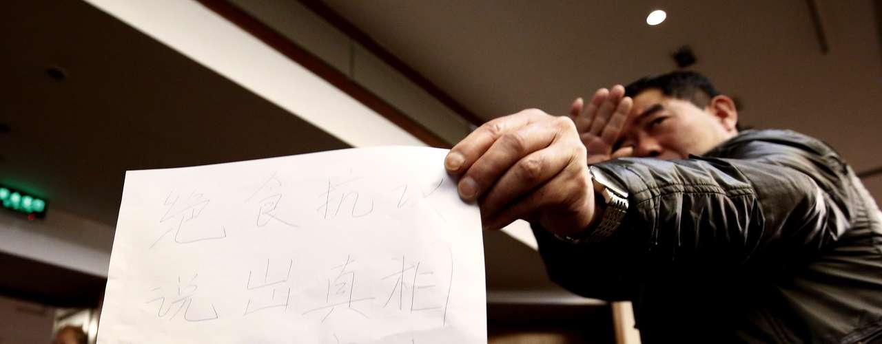 Homem mostra papel para a imprensa com mensagem das famílias dos passageitos que amaeaçaram greve de fome em 18 de março